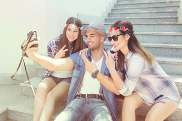 Three young friends are having fun on summer vacation. They are sitting on the outdoor steps while young man is taking a self-portrait with two girls showing peace sign.