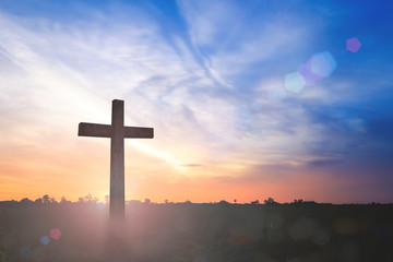 Good Friday and Easter Sunday concept: Silhouette the cross on sunset background.