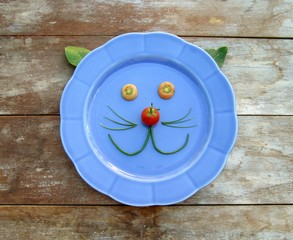 Smiling Veggie Cat Face - spinach, carrot, green onion and a cherry tomato making a face on a vintage blue plate.