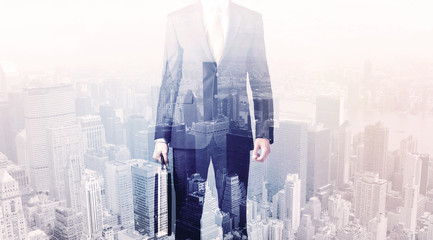 Business man standing on roof with city in the background