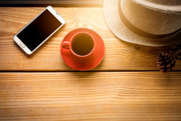 Coffee in red cup on wooden plank with cell phone and hat in mor