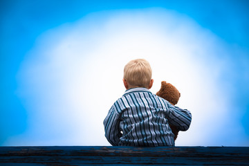 Child and Teddy at the Roof / Little boy in pajama cloth sitting at a wooden roof with the teddy bear in his arm in front of a bright light at the dark blue sky