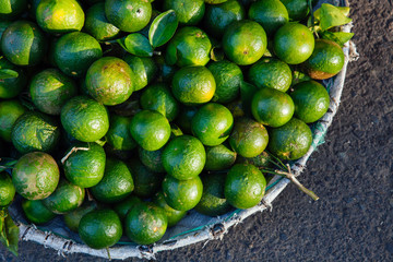 Basket with fresh limes at the street market, Vietnam