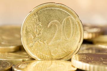 Twenty euro cent standing between other coins