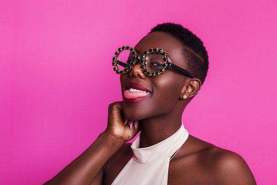 Funny african girl with tongue stuck out wearing strange glasses