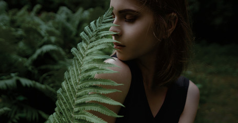 Young woman with fern