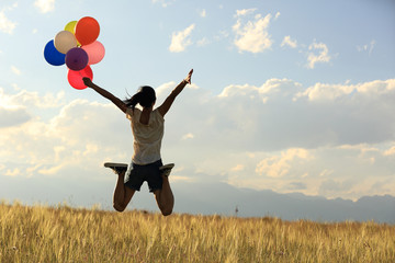 cheering young asian woman jumping on grassland with colored balloons