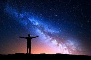Acrylic Prints Universe Night landscape with Milky Way. Silhouette of a standing young man with raised up arms on the mountain. Beautiful Universe. Travel background with blue night starry sky