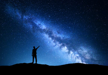 Milky Way. Silhouette of a standing man pointing finger in night starry sky on the mountain. Colorful night landscape with beautiful universe. Travel background with blue sky full of stars