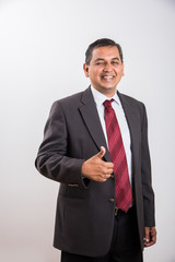 portrait of indian businessman showing victory sign or thumbs up as a symbol of success, successful indian businessman, portrait of confident mid age asian businessman showing victory sign