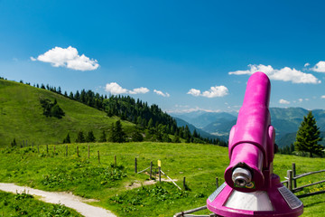 Pink telescope in close-up looking over green alp