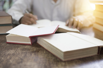 man reading book with textbook stack on wooden desk