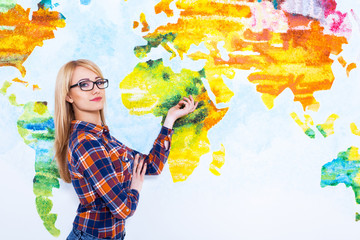 Look here! Attractive young women in glasses and casual wear pointing at the map of the world.
