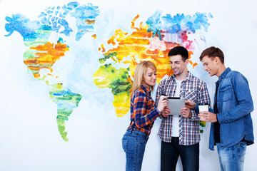 Look at here. Three beautiful students talking in front of wall painted like a map of the world.
