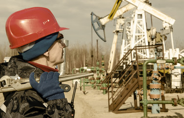 Portrait of man engineer in the oil field wearing red helmet and work clothes holding wrenches in his hand and radio in jacket pocket. Blurry pump jack background. Oil and gas concept. Toned.