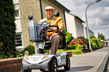 Elderly Person on Electromobile Wall mural