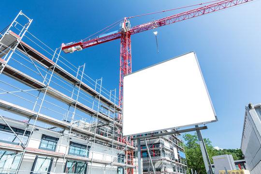 Leeres Schild auf Baustelle für modernen Neubau mit Gerüst und Kran im Hintergrund