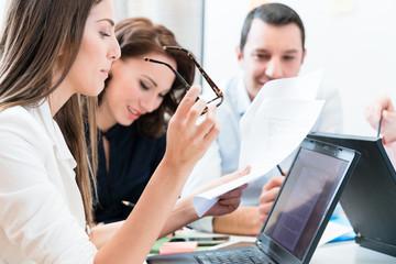 Frauen und Männer in Büro lesen Dokumente