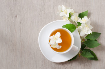 Top view of a mug of herbal tea and jasmine flowers on a wooden table, space for text