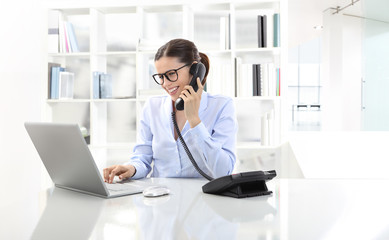 smiling woman in office at desk with computer, talking on the ph