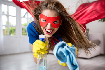 Attractive woman superhero flying through the room with a mop