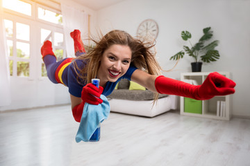 Pretty woman superhero flying through the room with a mop