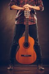 Guitarist is standing with wooden guitar.