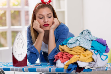 Lazy woman looks at laundry on ironing board
