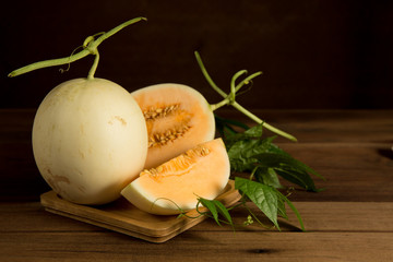 Yellow cantaloupe melon on the wooden background.