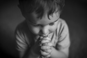 Cute Young Boy Praying in Black and White / A cute young boy praying with hands clasped, in black and white.