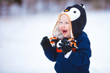 Young Boy Playing in Snow / A young boy wearing a winter coat and hat laughs as he plays in the snow.