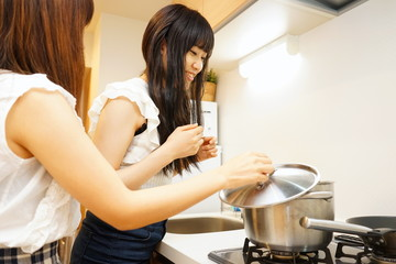 Two young Japanese women cooking in kitchenシェアハウスの台所で料理をする若い日本人の女性 民泊 寮生活