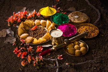 holi festival food with colours, indian festival holi, samosa, kachori, laddu, gujiya, palash flower, thandai, farsan, chana masala, puran poli or roti, indian festival of colours called holi