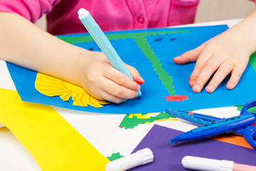 Child makes application of colored paper