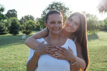 Daughter with mother hugging in nature. Unconditional love.