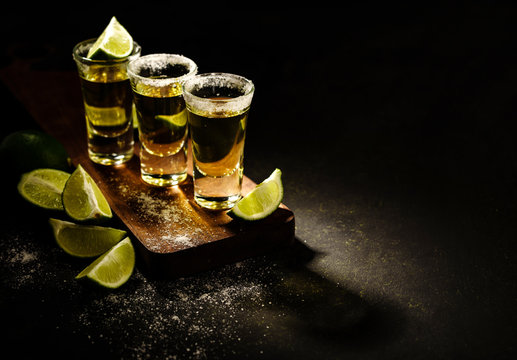 Mexican Gold Tequila with lime and salt on wooden table, selective focus. Copyspace.