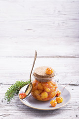 Cloudberry jam in glass jar on wooden background