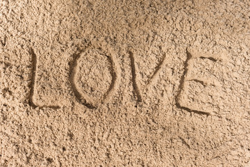 love - an inscription a hand on sea sand