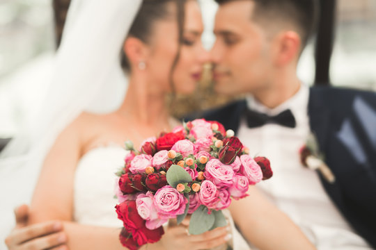 Portrait of happy newly wedding couple with bouquet