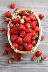 Fresh strawberry in basket  on old wooden table.  Top view, high resolution product. Harvest Concept