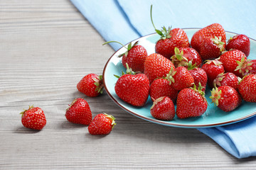 Ceramic plate with strawberries on old wooden table. Close up, high resolution product. Harvest Concept