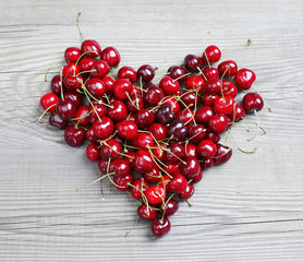 Heart made from cherry on wooden table. Fruits diet concept. Top view, high resolution product.