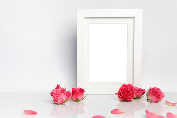 Blank photo frame and pink roses on white table background