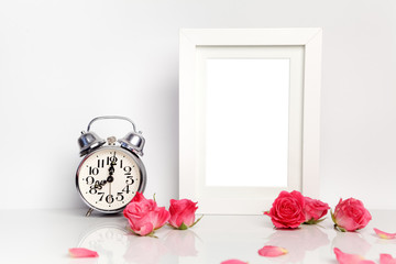 Blank white frame, pink roses and alarm clock. Mock up.