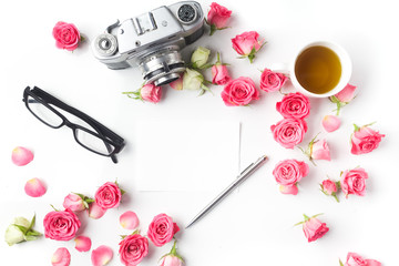 Vintage camera pink roses and note on white background. Flat lay. Top view