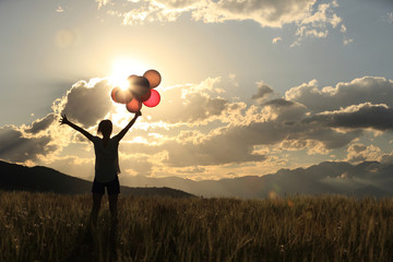 cheering young asian woman on sunset grassland with colored balloons