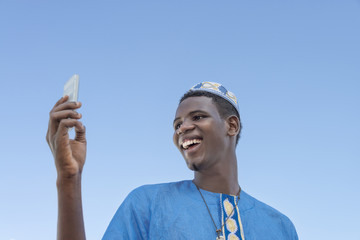 Young man making a self-portrait with his mobile phone under a blue sky
