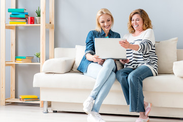 Carefree woman using computer with parent