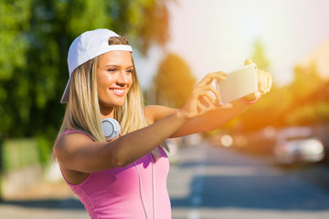 Beautiful young woman taking a selfie in the street