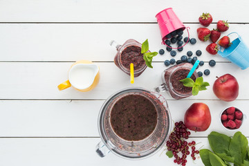 smoothie in mason`s jars, mint leaf,  colorful baby buckets, berries, apples, redcurrant, spinach, bowl of a blender with drink, top view